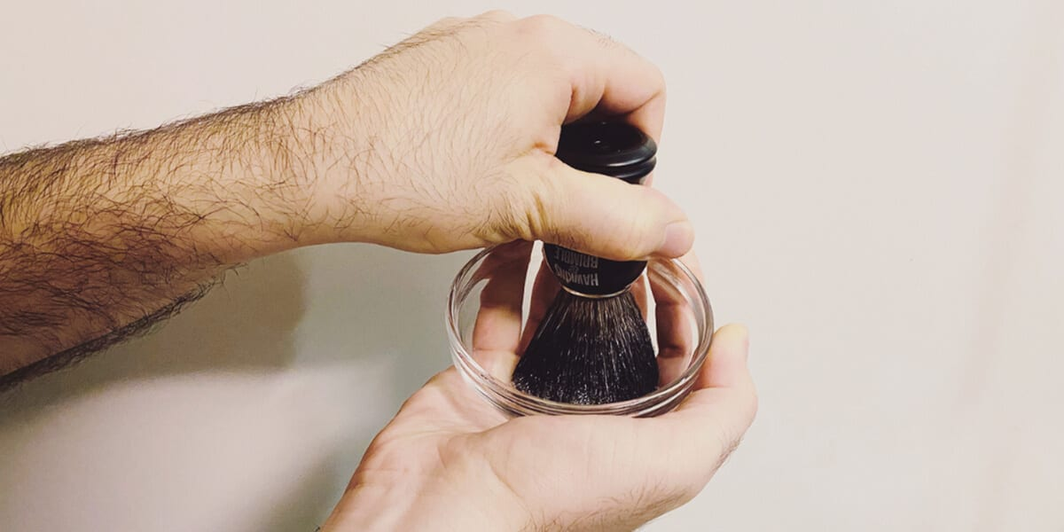 a hand holding beard brush and lathering bristles in bowl of shaving cream