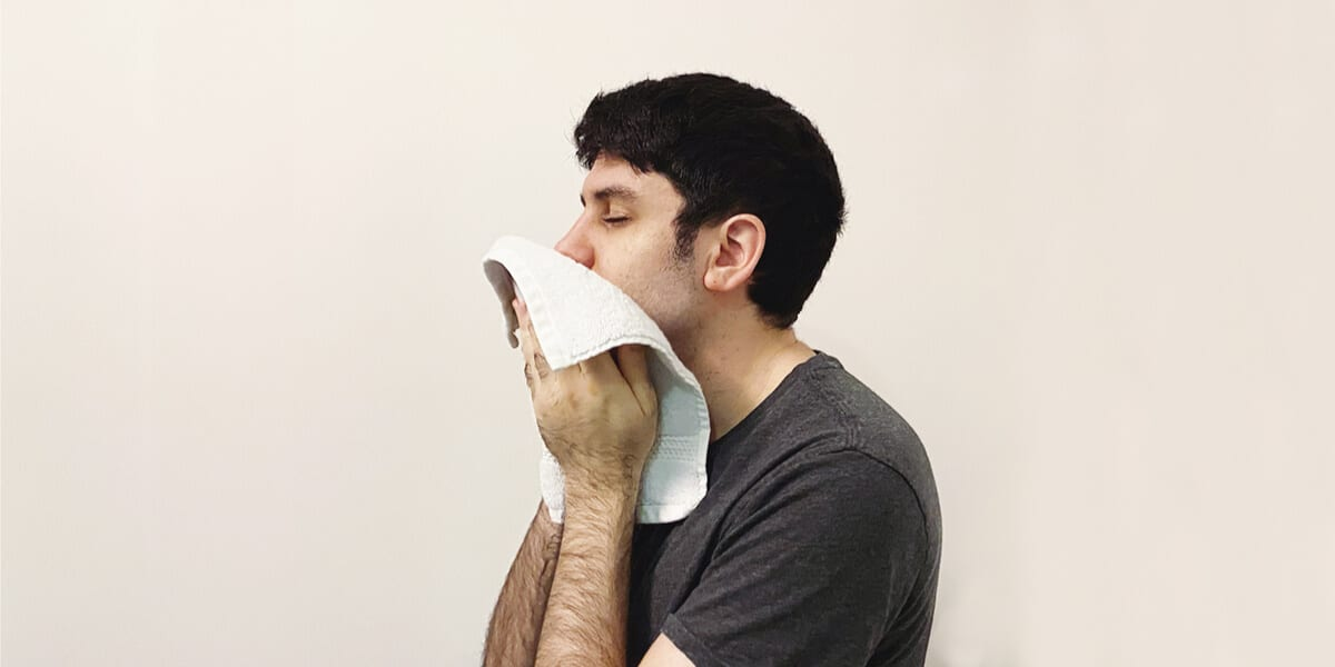man wiping face with washcloth