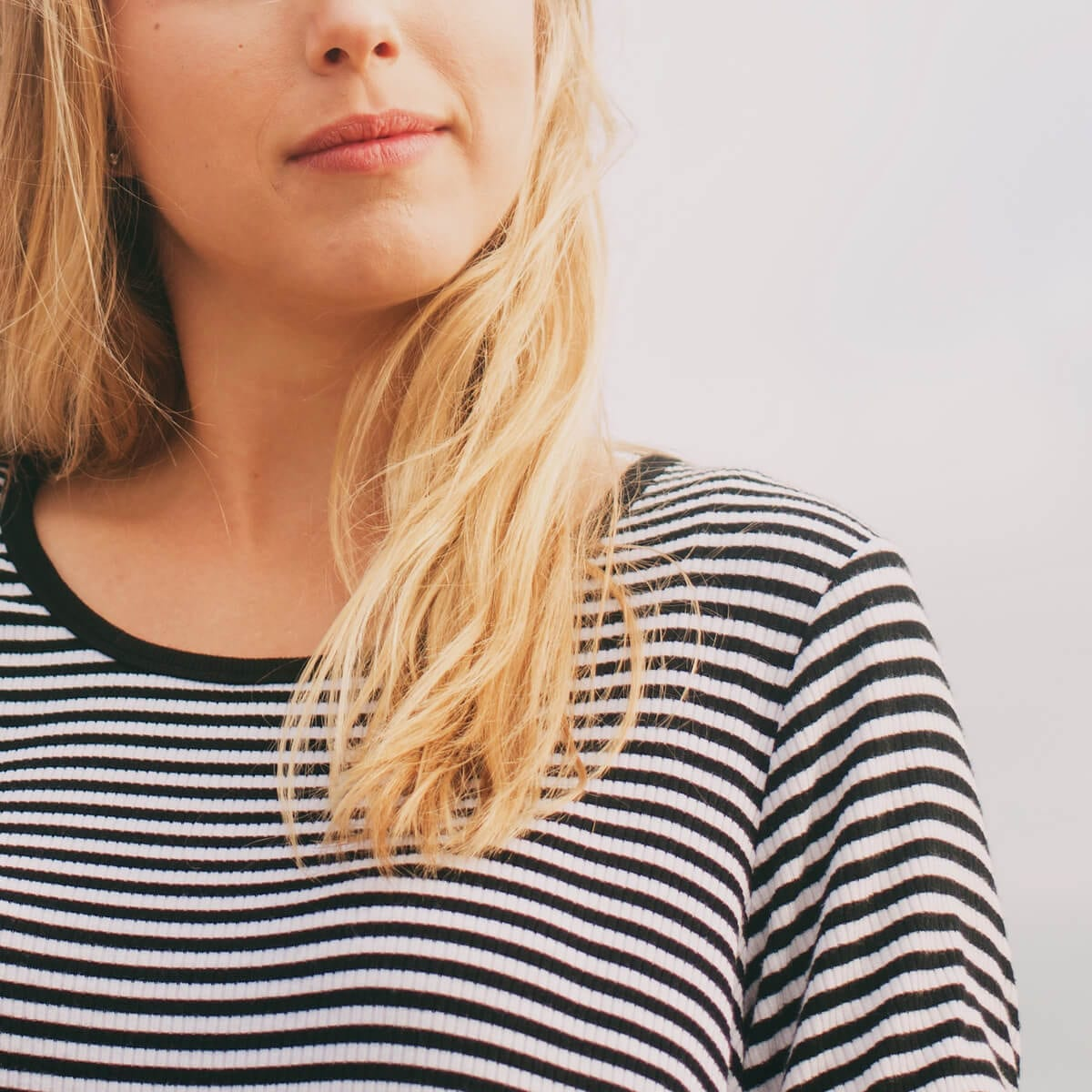 blonde woman in a black and white striped shirt