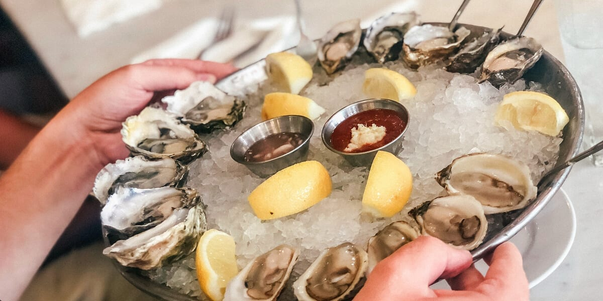 A plate of oysters, lemons, cocktail sauce, ice