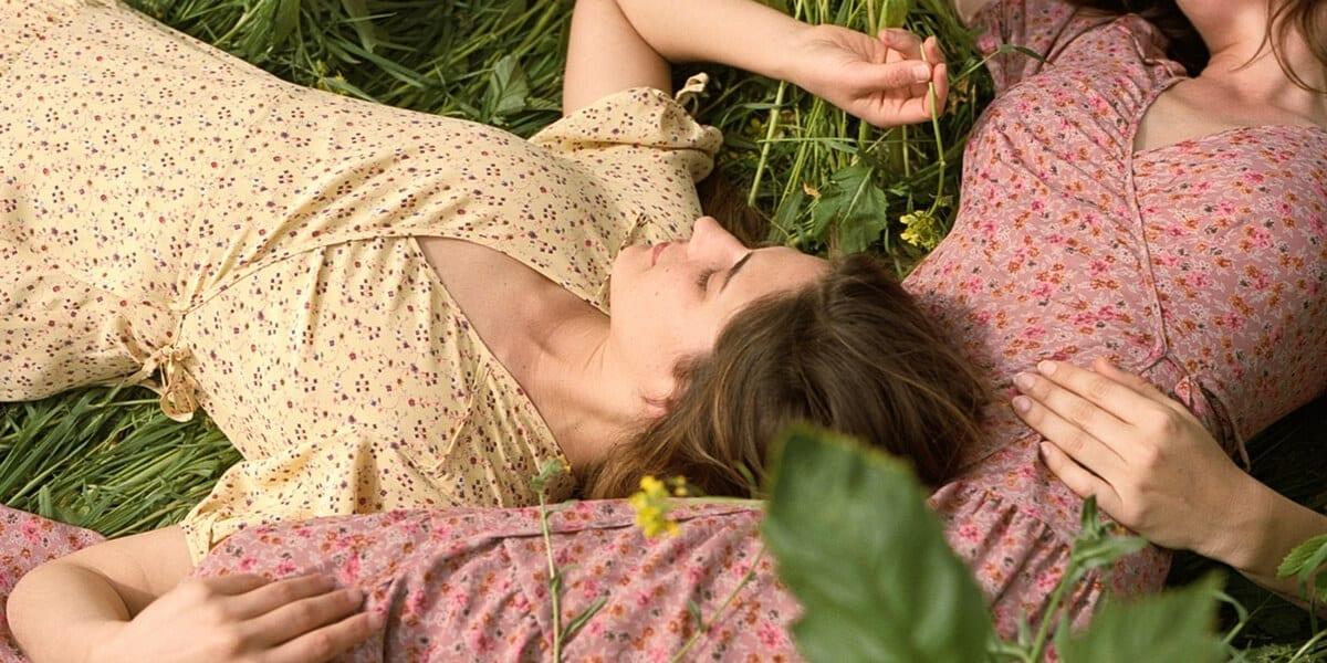 two women laying in the grass