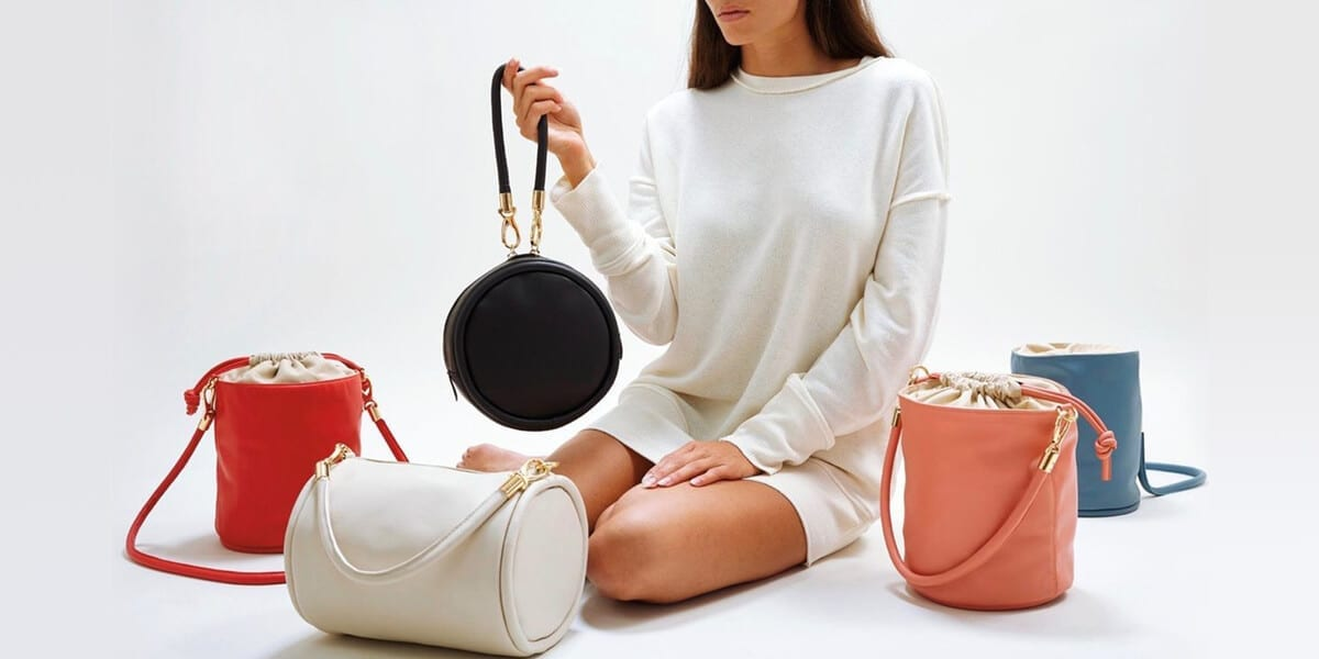 woman in white sweater dress holding black handbag with white, red and pink handbag in front of her