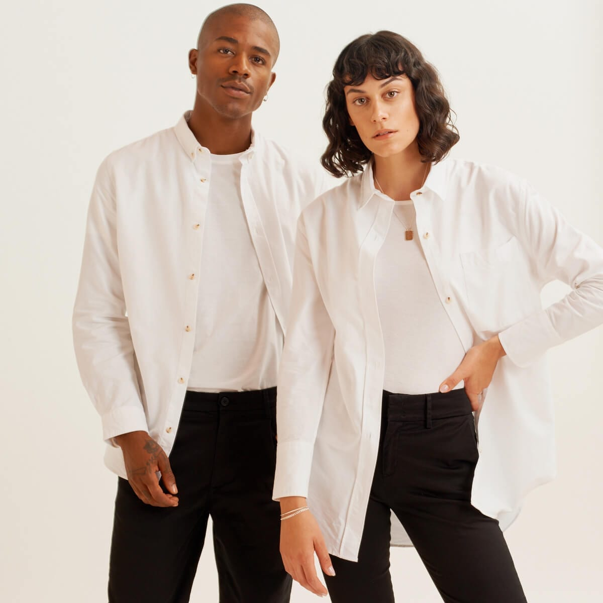a man and a woman in white coat, white sweater, black pants