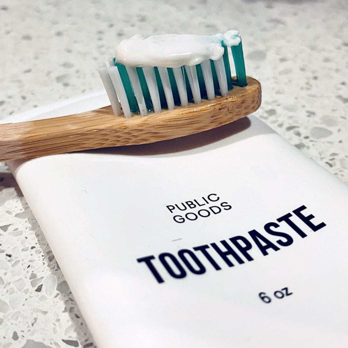 tube of public goods toothpaste, bamboo toothbrush with toothpaste on the wet bristles
