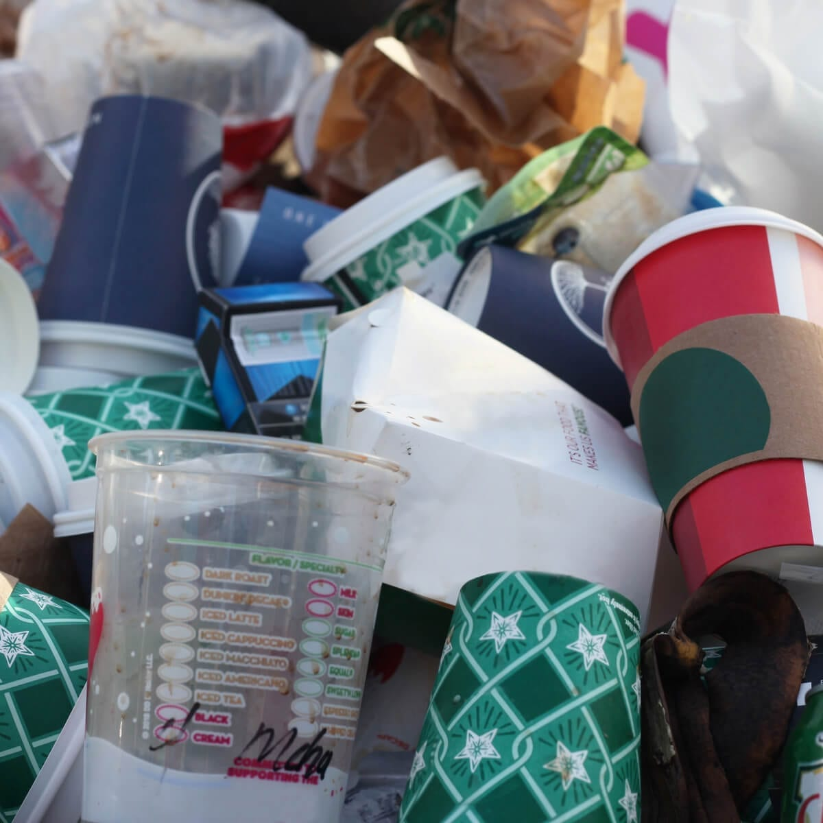 a pile of recycled materials including plastic cups, coffee cups