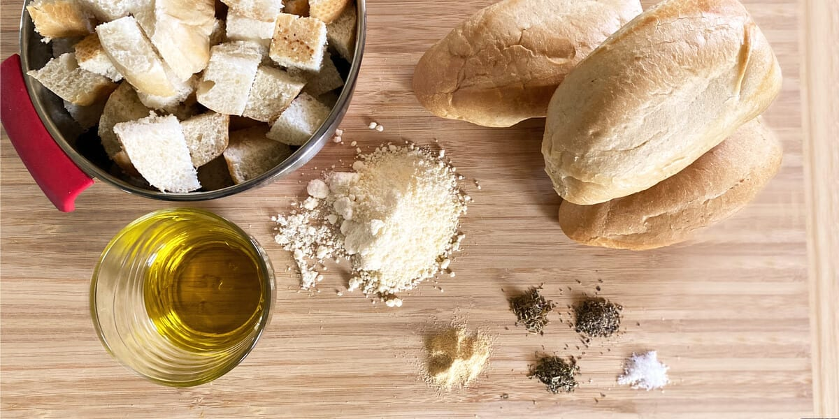 cubed bread in a mixing bowl, loaf of french bread, cup of olive oil, oregano, italian seasoning, garlic powder, parmesan cheese