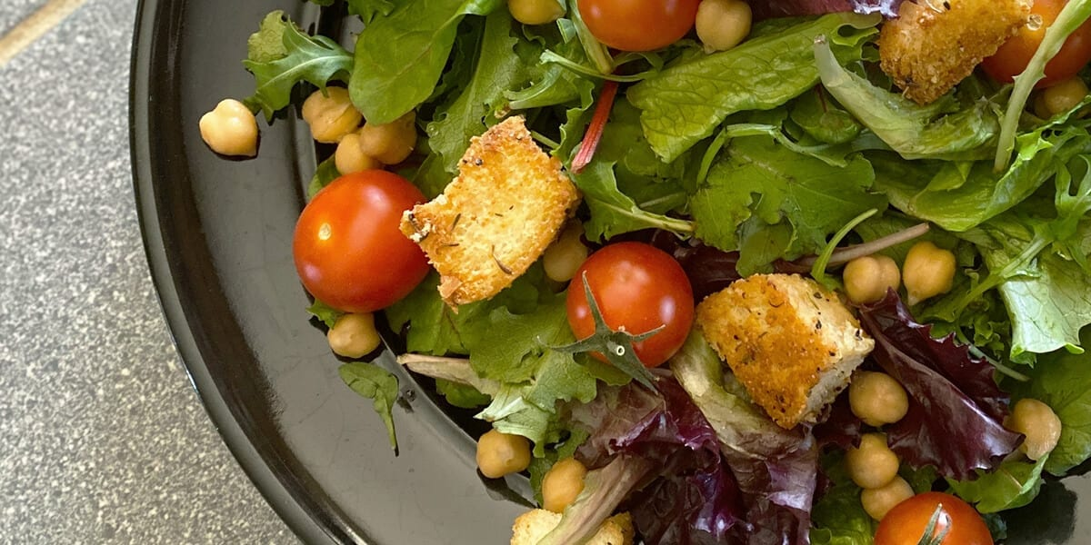 spring mix, cherry tomatoes, croutons, chickpeas, salad on a plate