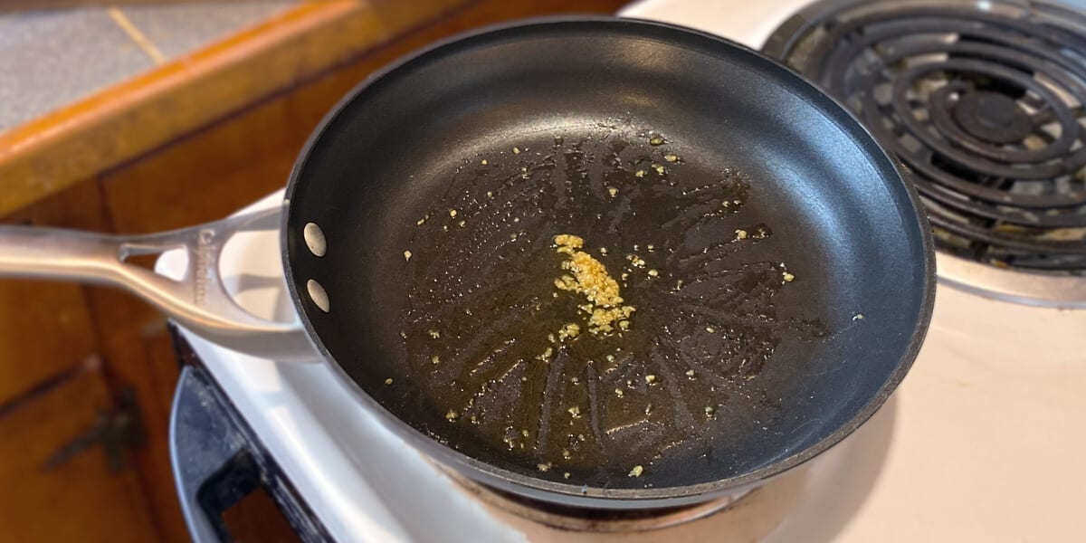 olive oil and minced garlic in a frying pan on the stovetop