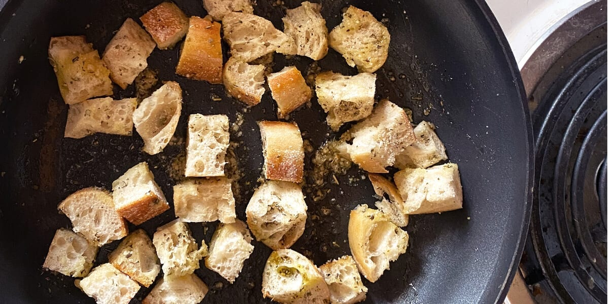 croutons with olive oil and herbs in a frying pan on the stovetop
