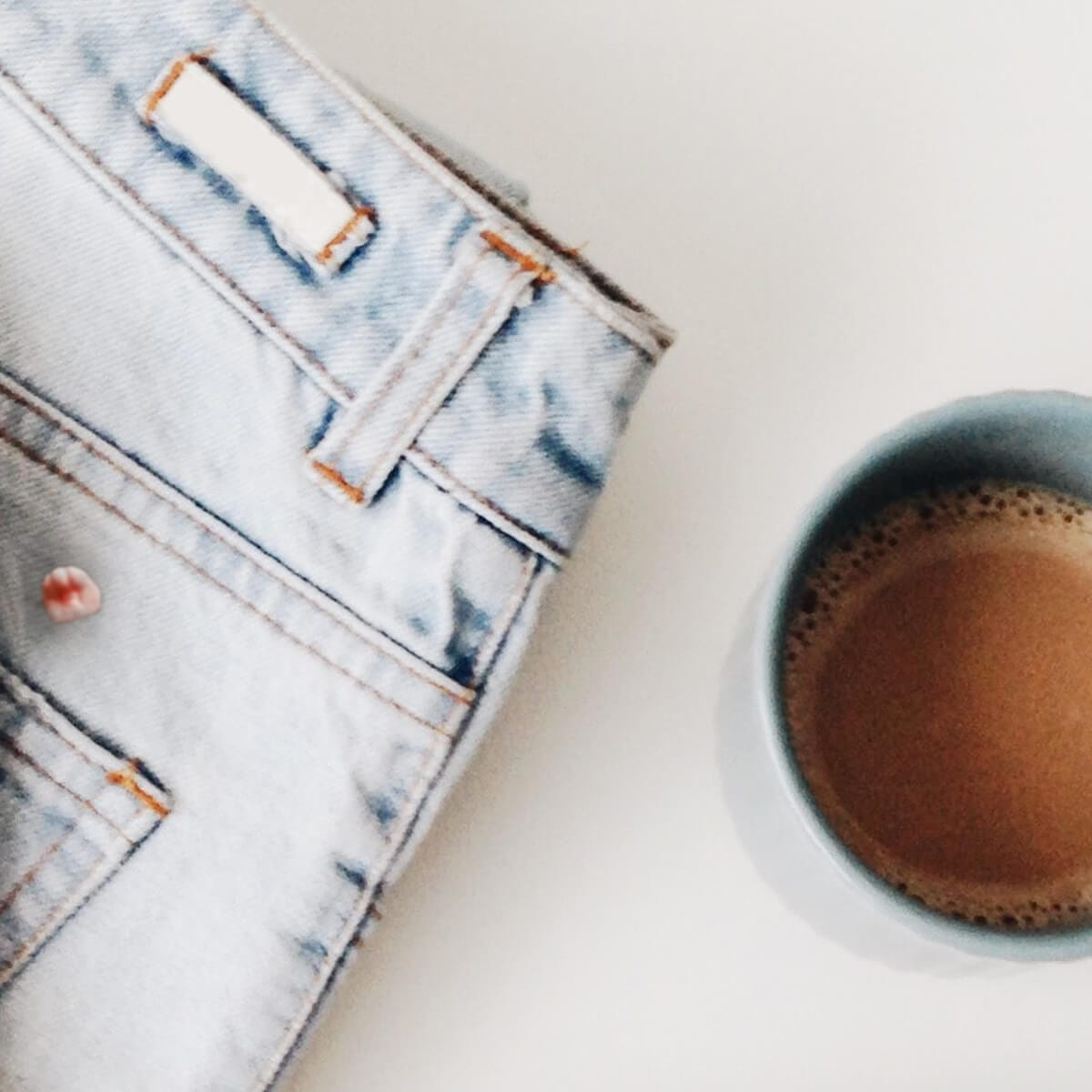 White washed jeans with gum on them, cup of coffee