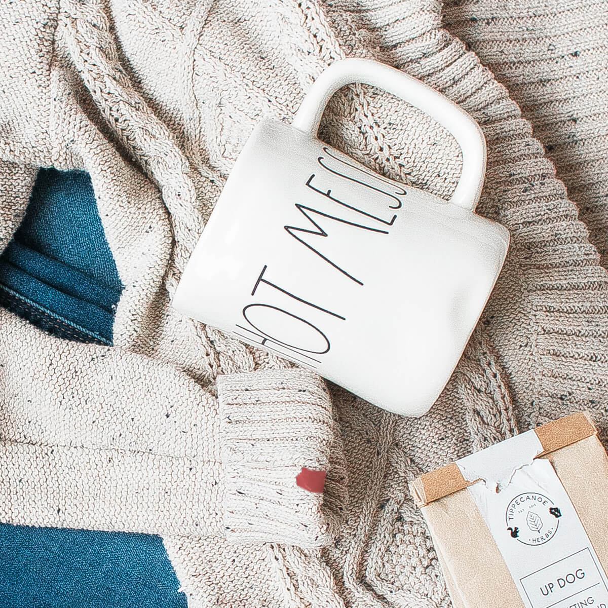 Knitted sweater with red nail polish on it, blue jeans, coffee mug