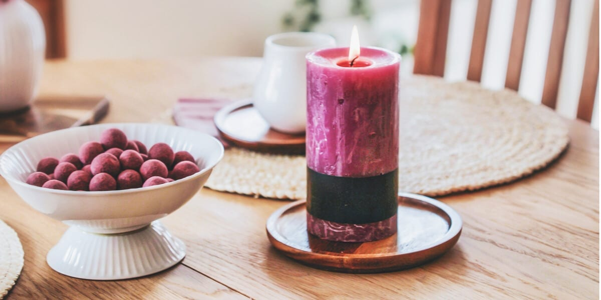 candles on a table with berries