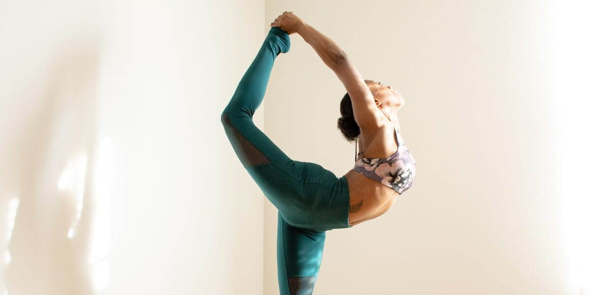 woman doing yoga stretch with leg in air