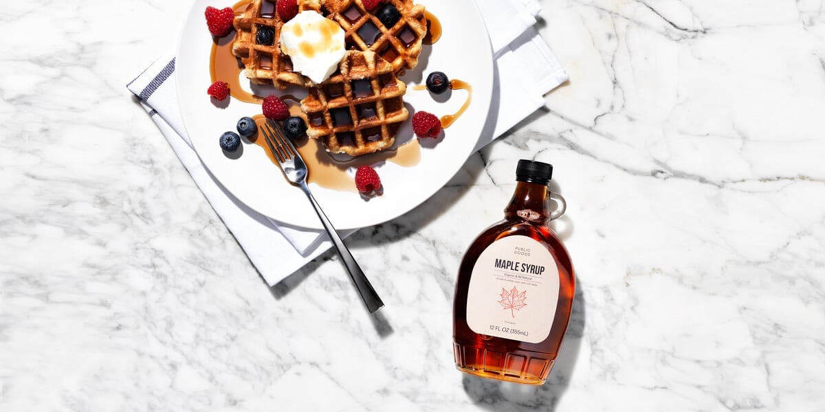 bottle of public goods maple syrup, waffles topped with maple syrup butter blueberries and raspberries on a plate with a fork, granite countertop