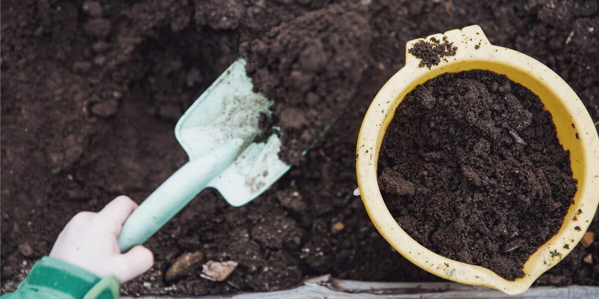 hand digging up soil with a shovel and putting it into a yellow bucket