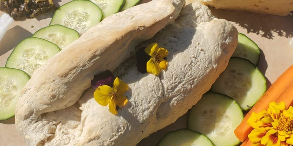 freshly baked bread without yeast, sliced cucumbers, yellow and purple flowers