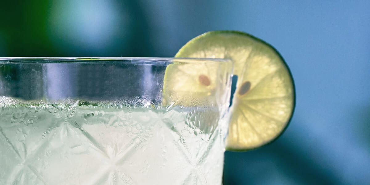 glass of aloe vera juice with a lime garnish
