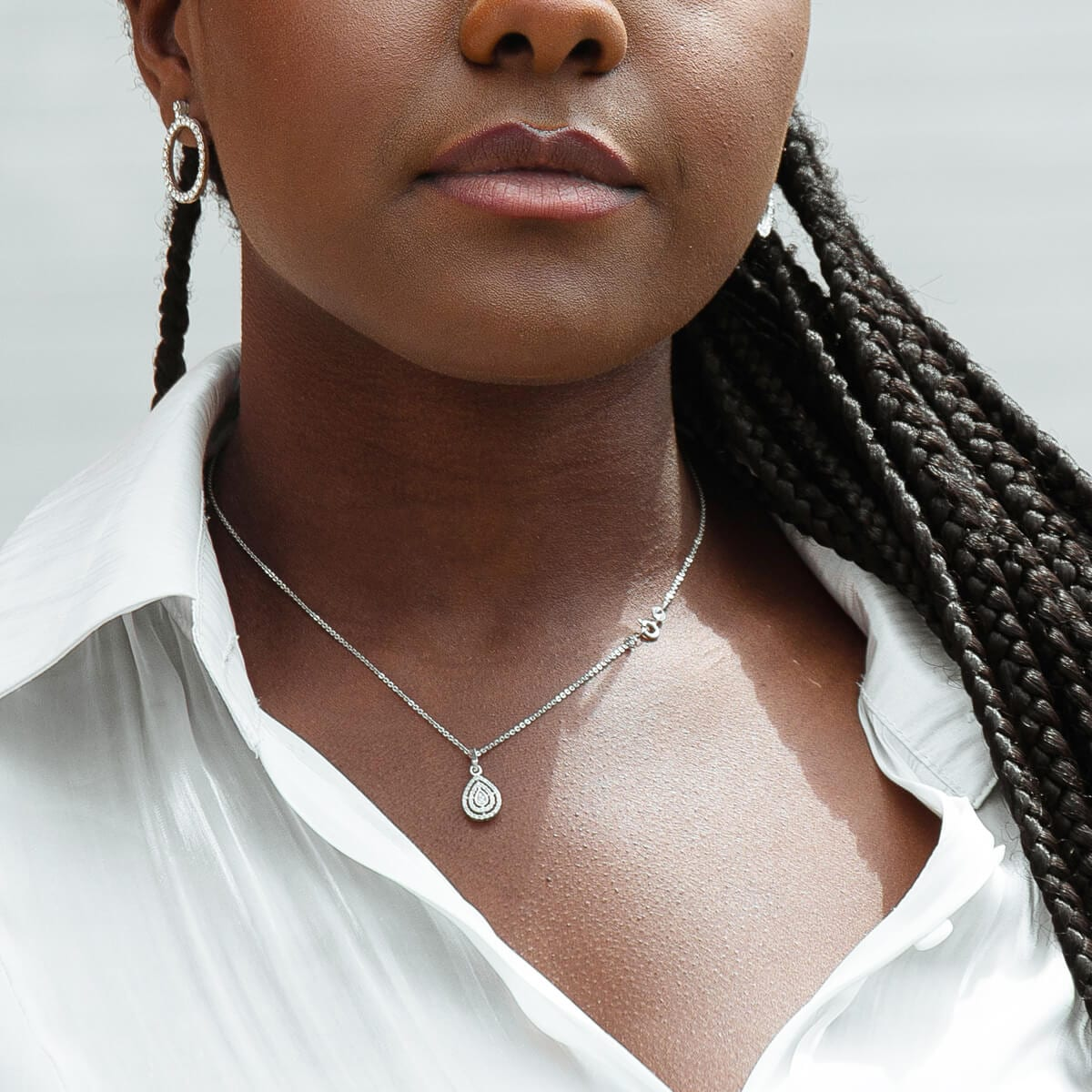 black woman with braids a necklace and an earring
