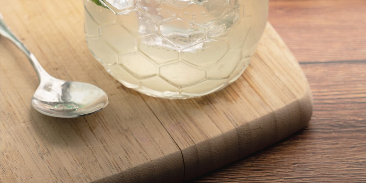 aloe vera gel in glass jar, spoon, wooden cutting board