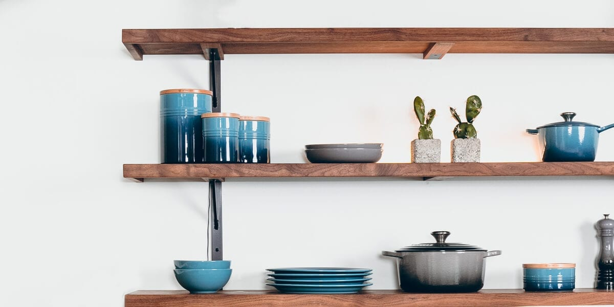 plates, bowls, plants, pots and a pepper shaker on a shelf