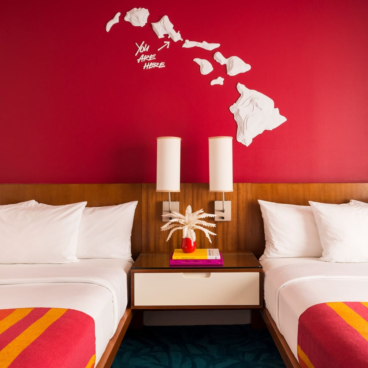 "outline of Hawaii on a wall with ""You are Here"" and an arrow pointing to the island of Waikiki, a bed two lamps and a plant"