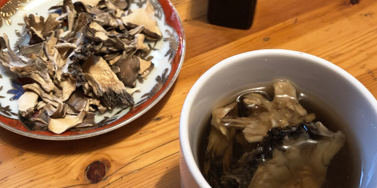 cup of hot maitake tea, maitake mushrooms on a plate