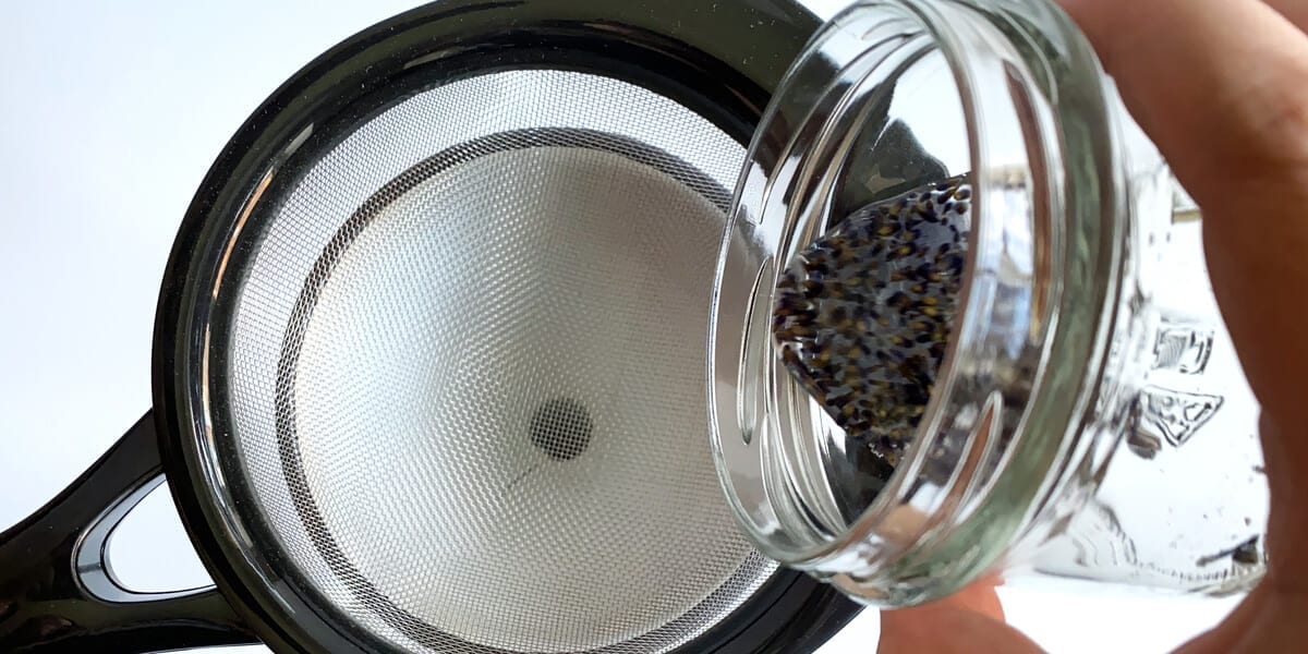 lavender oil being poured into funnel