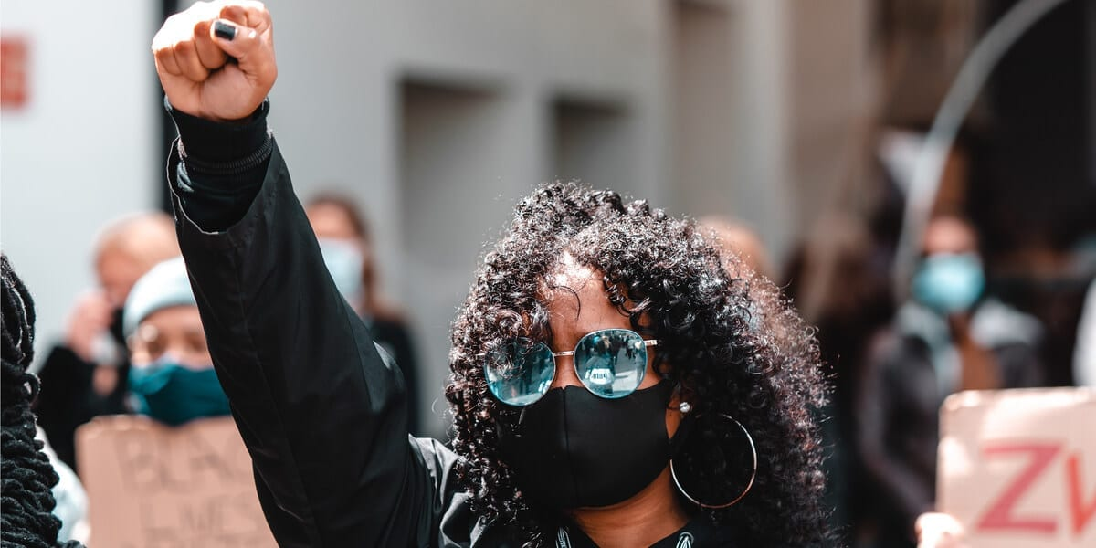 black lives matter protester in a mask with a group of other protesters