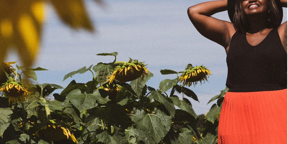 woman making an exasperated face in front of sunflowers