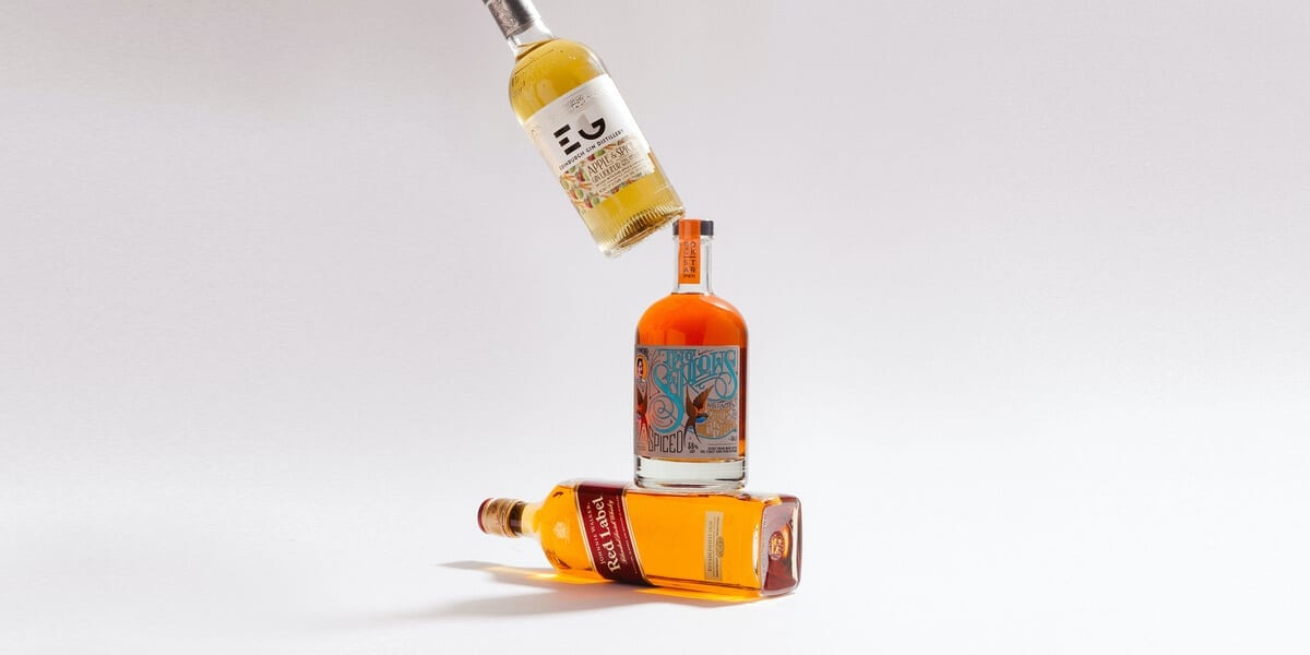 three alcohol bottles stacked on top of each other