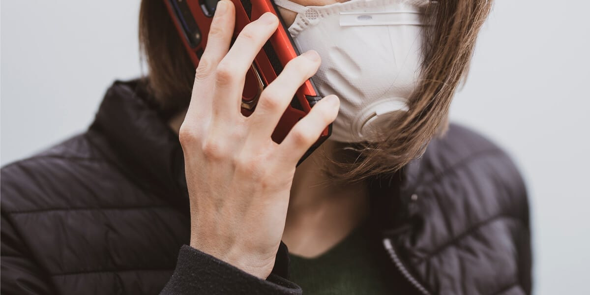 white woman wearing a mask talking on a cell phone