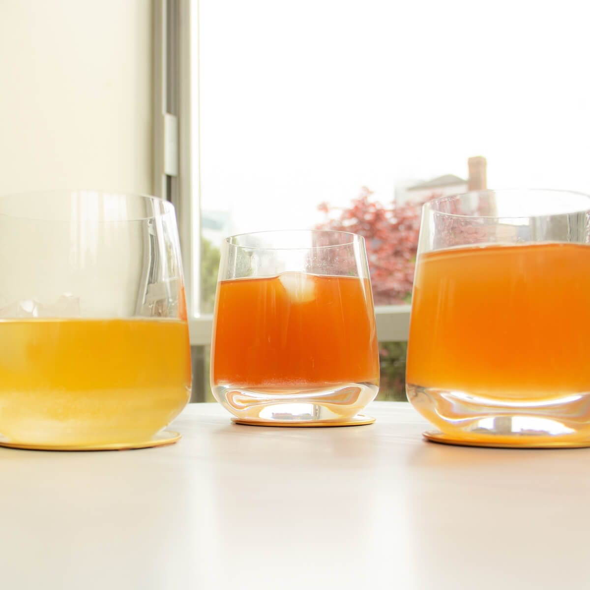 glasses of switchel and shrubs sitting by a window