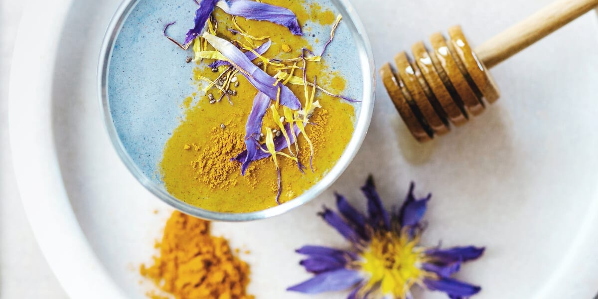 bowl filled with turmeric powder, purple plant, honey on a wooden server