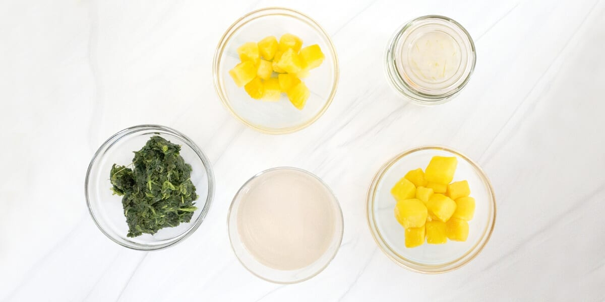 bowl of frozen pineapple, bowl of frozen mango, bowl of spinach, bowl of coconut oil, jar of aloe vera gel