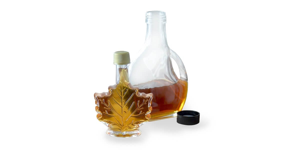 bottle of maple syrup in a maple leaf container and a bottle of maple syrup in a round container
