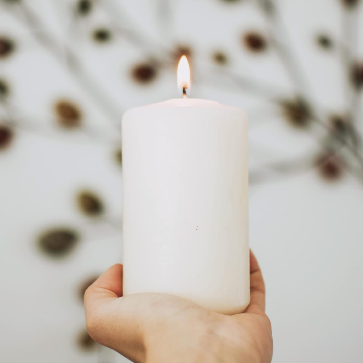 a white candle with a burning wick