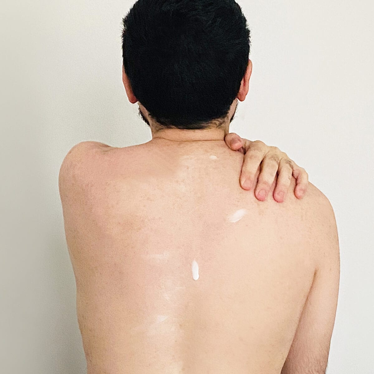 man putting lotion on his back