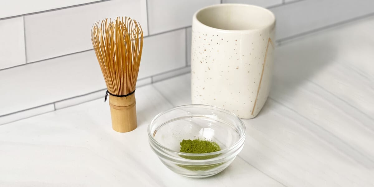 matcha powder in a glass bowl next to a whisk and mug