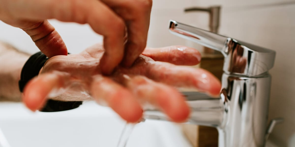 washing hands with soap in a kitchen sink