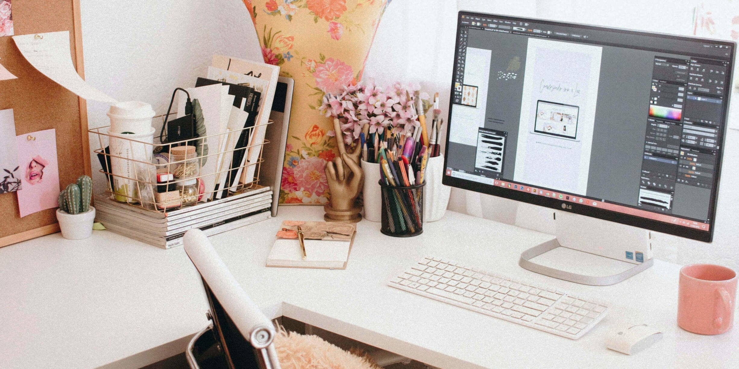 computer on a desk with pink mug, chair, pens and pencils in a container, flowers, basket, corkboard