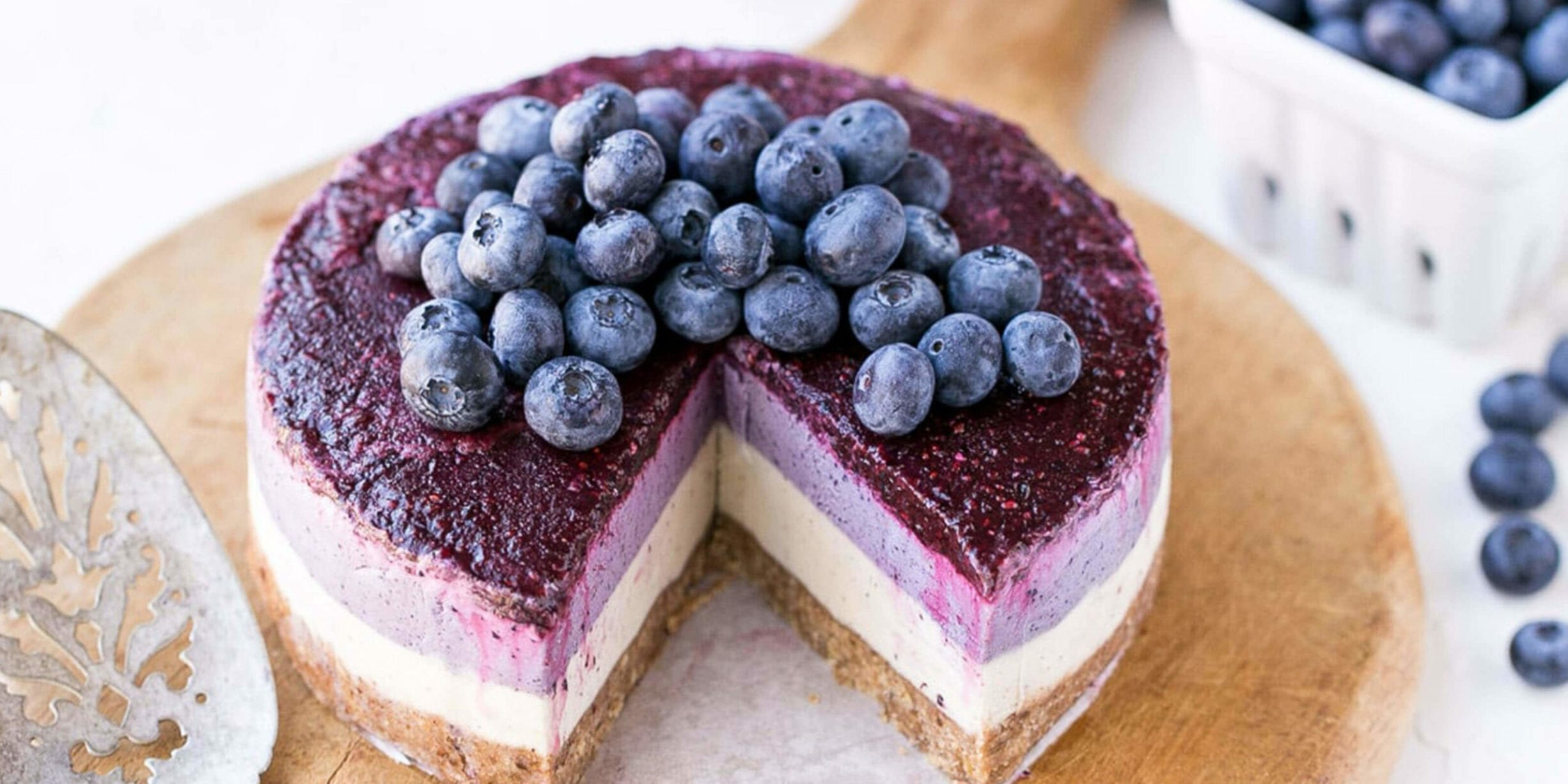 a vegan blueberry cheesecake pie topped with blueberries and blueberry sauce on a serving plate