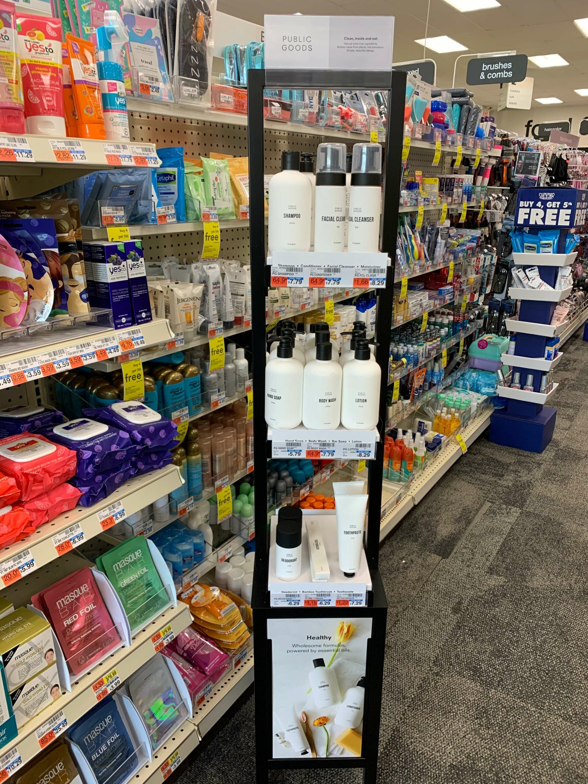 CVS tower featuring public goods shampoo, facial cleanser, hand soap, body wash, lotion, deodorant, toothbrush, toothpaste