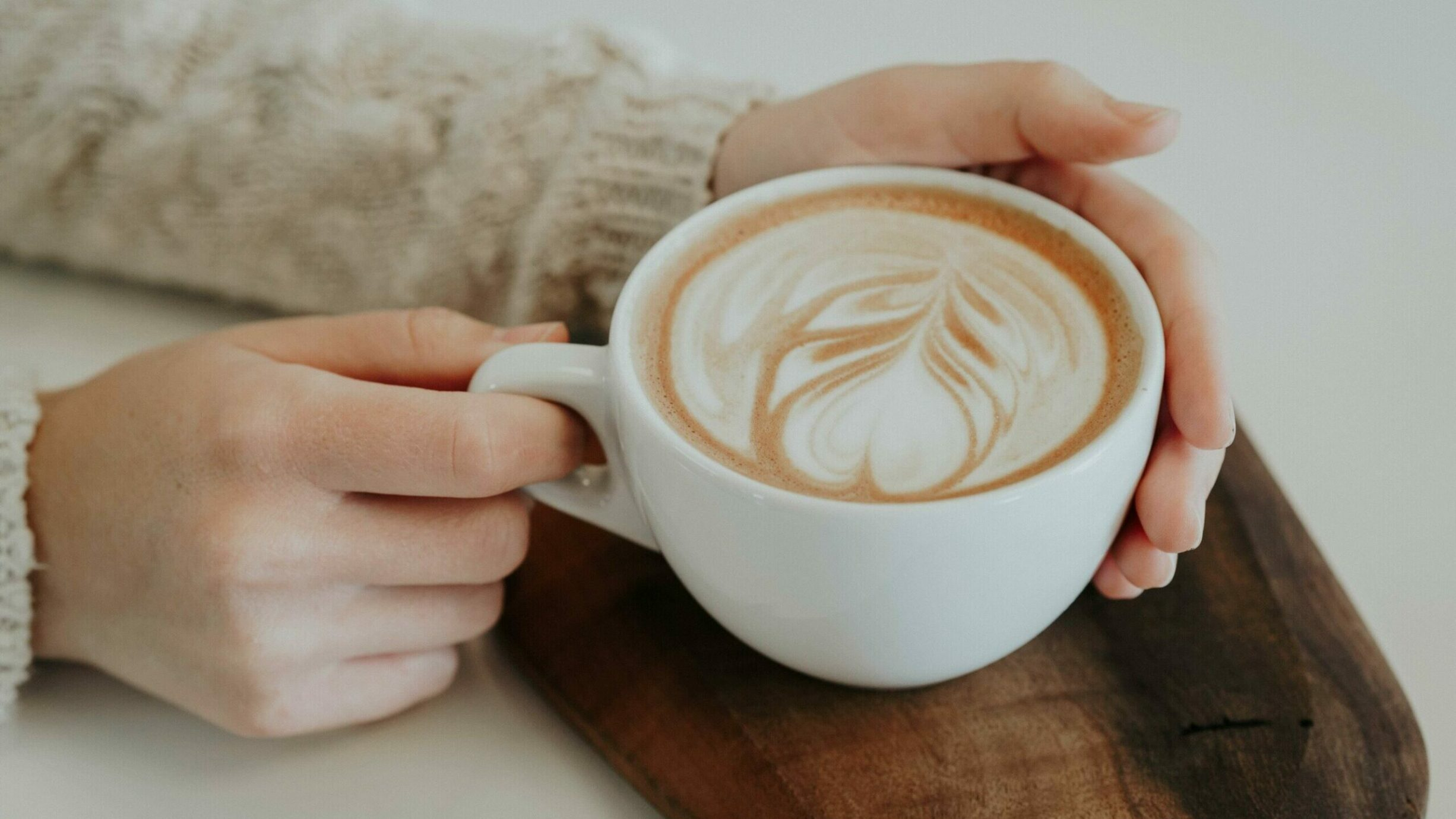 hands holding a latte in a white coffee mug