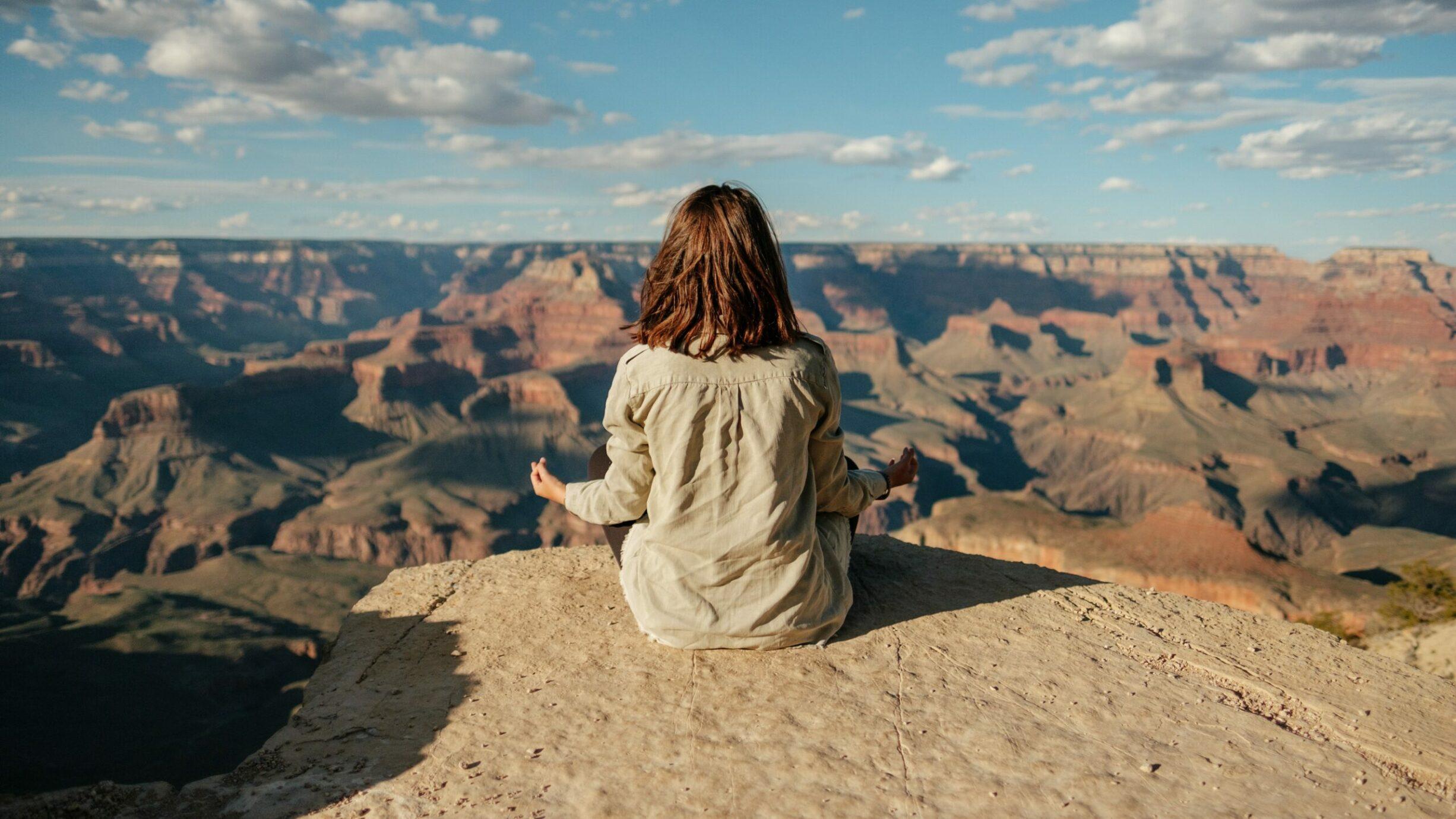 woman meditating overlooking canyon