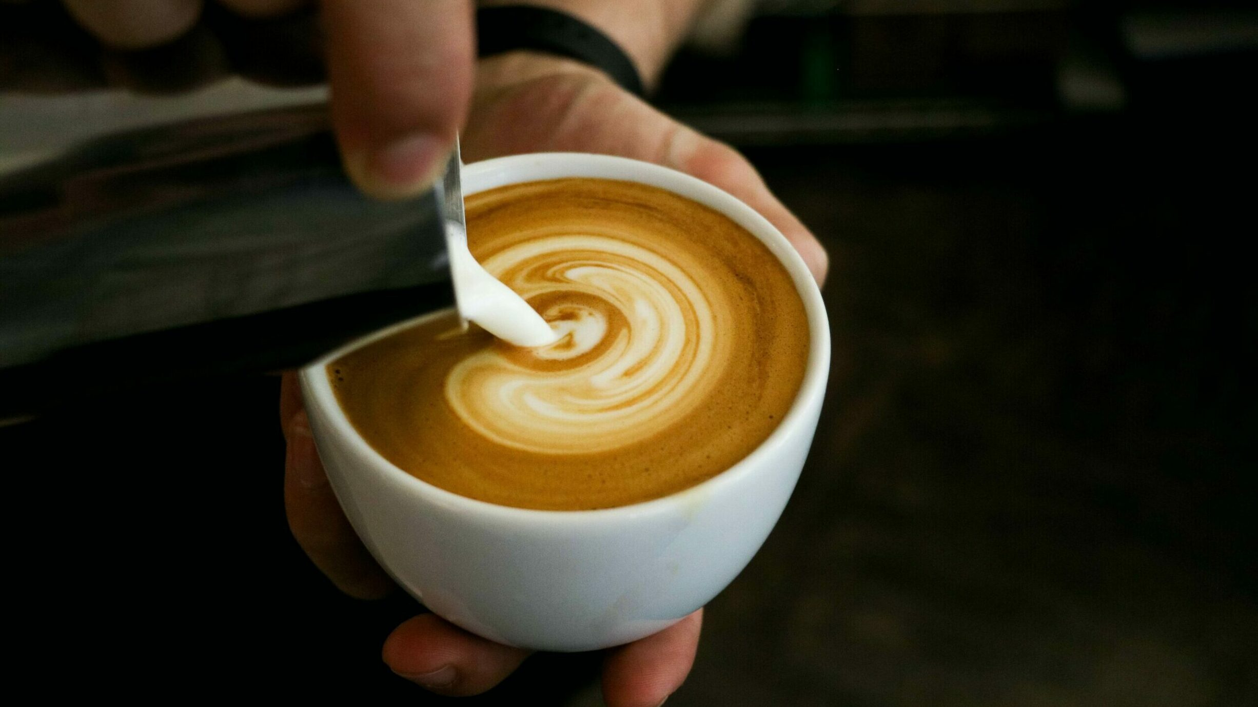 pouring steamed milk into a cup of espresso