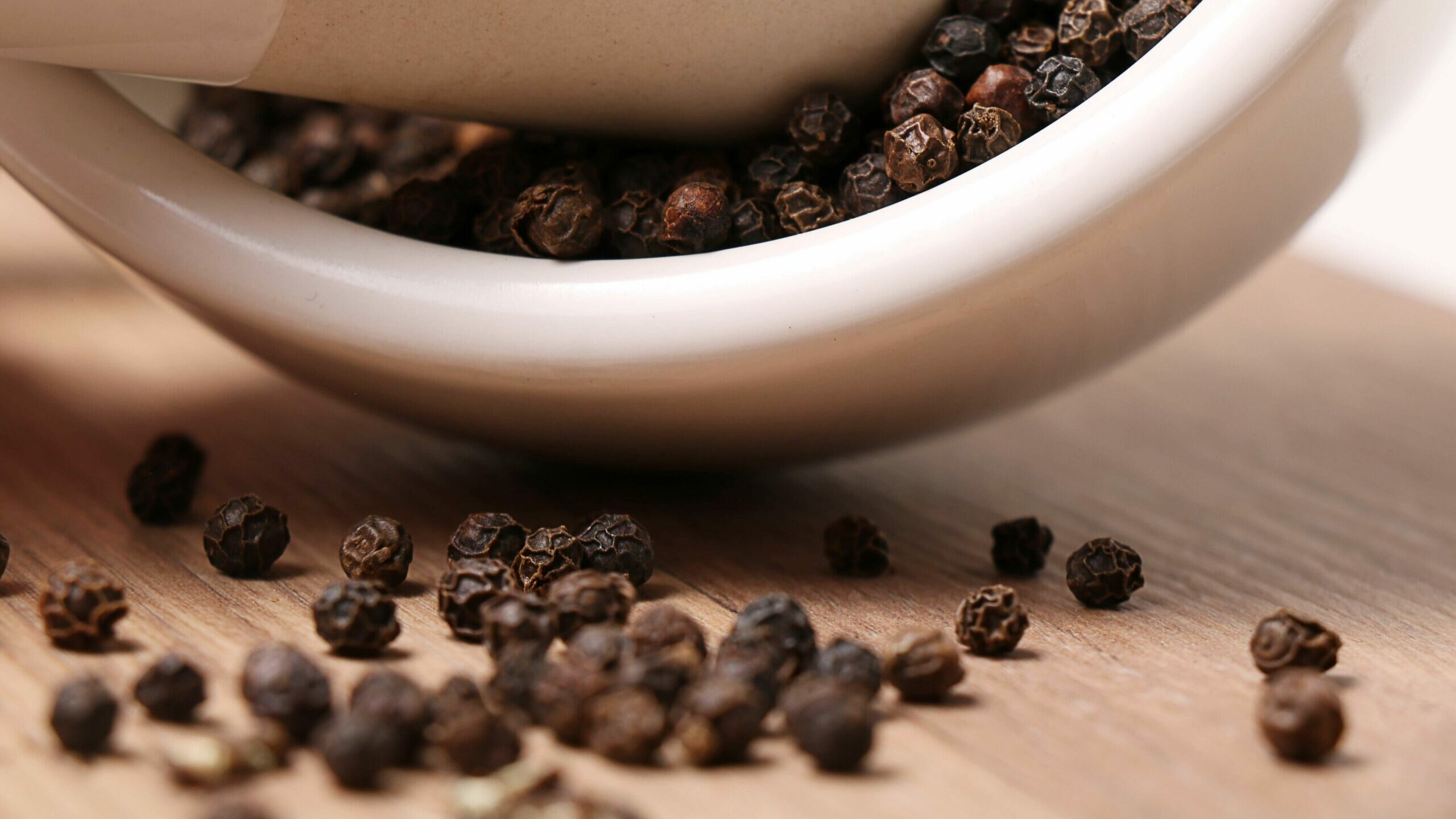 black peppercorns in mortar and pestle bowl