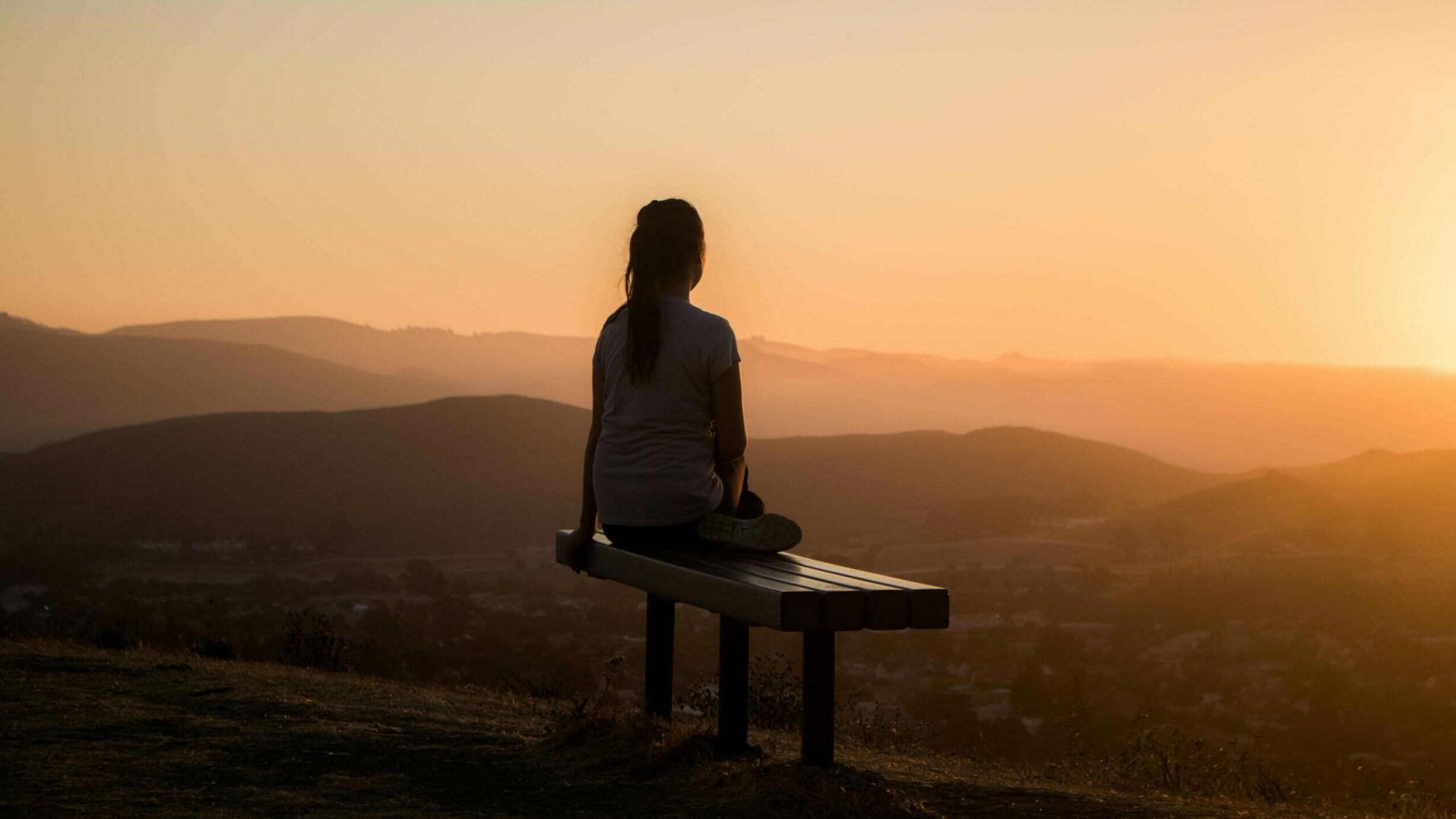 woman meditating on a bench overlooking the mountains during sunset