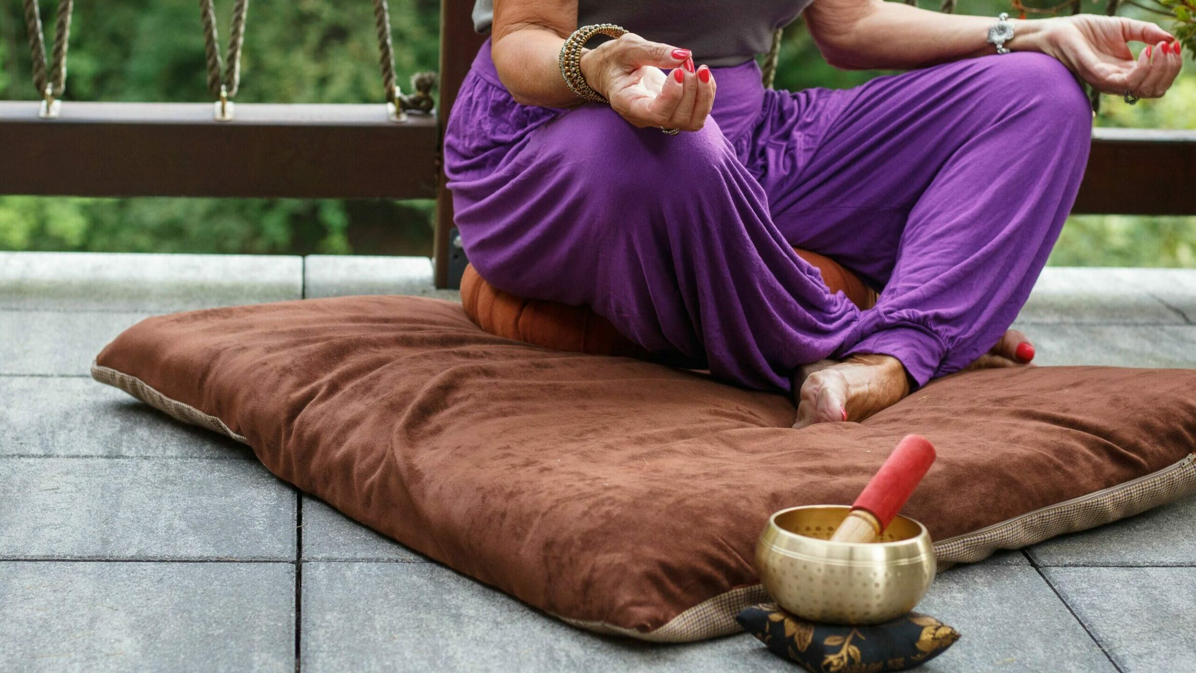 person meditating on meditation pillow, sound bowl