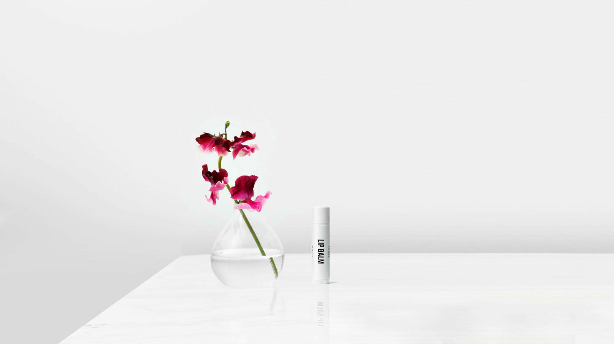 lip balm on a white table next to flowers