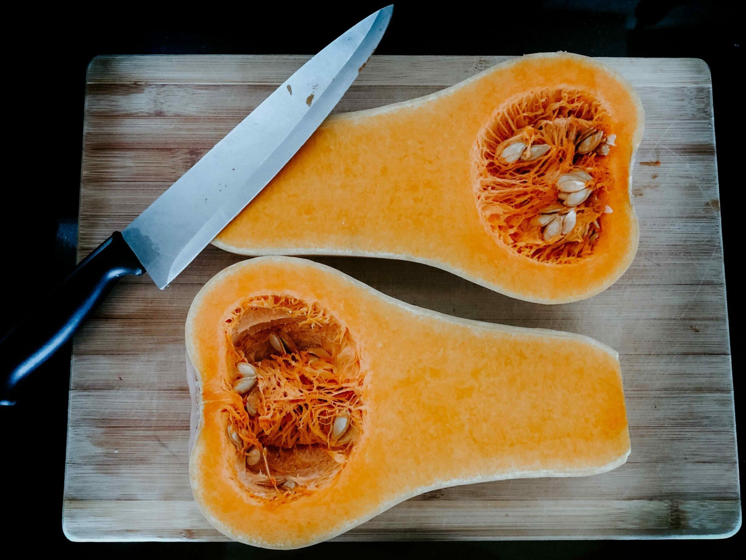 butternut squash cut in half on a wooden cutting board, sharp knife